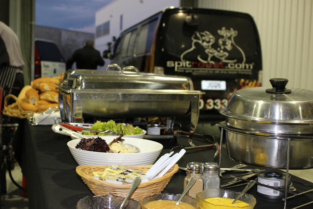 Buffet food set out on a table in a warehouse with Spitroast.com van in the background